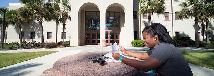 Student studying outside building